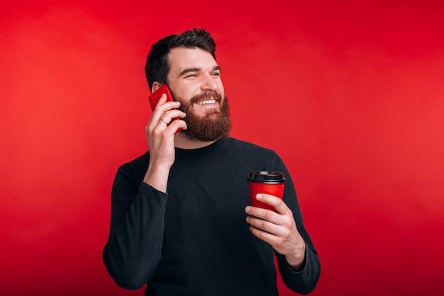 Foto de jovem alegre falando no smartphone e bebendo café