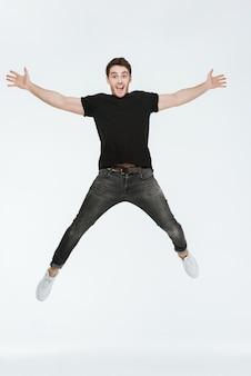 Foto de jovem alegre vestido com uma camiseta preta, pulando sobre um fundo branco, olhando para a câmera.