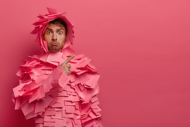 Foto de jovem aponta descontente, demonstra resultado ruim para os colegas de trabalho, franze os lábios, usa roupa engraçada de papel feita de adesivos, não gosta de alguma coisa, mostra espaço de cópia na parede rosa