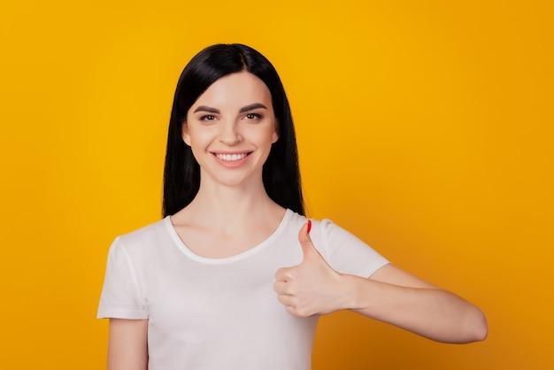 Foto de jovem atraente com sorriso positivo e feliz mostrando o polegar para cima perfeito, como um anúncio isolado sobre um fundo de cor amarela