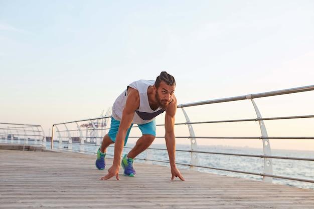 Foto de jovem barbudo desportivo à beira-mar, preparar-se para a corrida, parece ser boa.