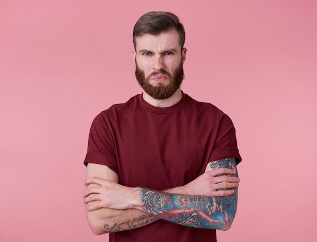 Foto de jovem bonito tatuado enojado homem barbudo vermelho em t-shirt em branco, fica com os braços cruzados sobre fundo rosa, carrancudo e olha para a câmera.