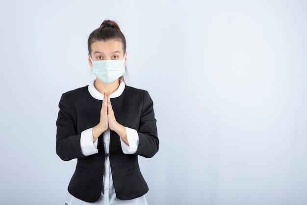 Foto de jovem com máscara orando sobre fundo branco. foto de alta qualidade Foto Premium