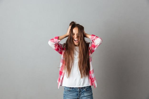 Foto de jovem de cabelos longos, gritando e tocando o cabelo