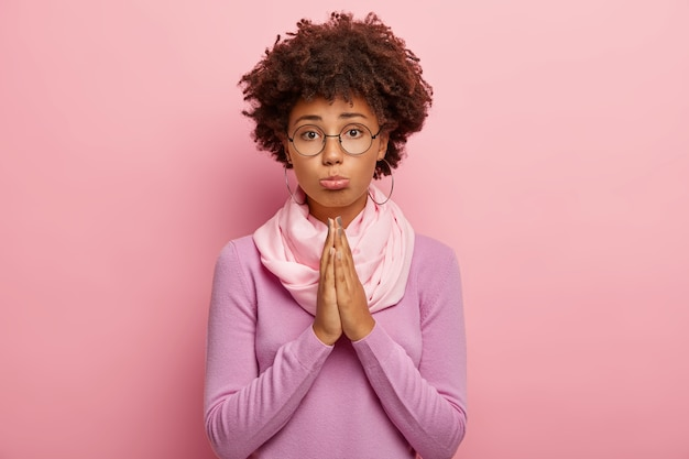 Foto de jovem de pele morena e penteado afro, tem expressão deplorável, mantém as palmas das mãos juntas, pede para dar mais uma chance, acredita no melhor, usa óculos redondos, macacão roxo