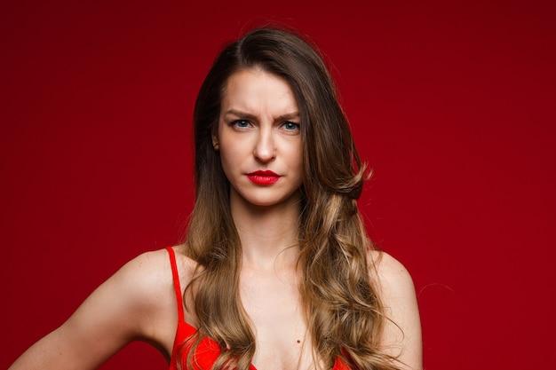 Foto de jovem descontente com mulher séria, carrancuda no fundo vermelho do estúdio com espaço de cópia para publicidade
