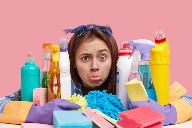 Foto de jovem descontente franze o lábio inferior com insatisfação, tem muito trabalho, abraça muitos detergentes químicos e esponjas