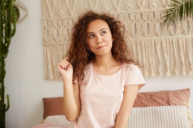 Foto de jovem desejosa, de pele escura, com cabelos cacheados, senta-se em uma cama e toca o cabelo, morde os lábios e desvia o olhar sonhadoramente, pensa na próxima festa.