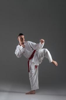 Foto de jovem desportista bonito na prática de quimono no karatê isolado sobre fundo cinza. olhe para o lado.