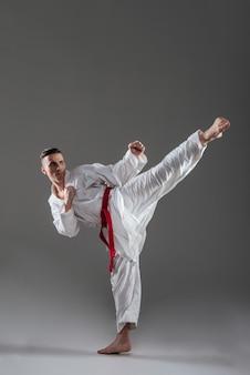 Foto de jovem desportista vestido de quimono pratica caratê isolado sobre fundo cinza. olhando para o lado.