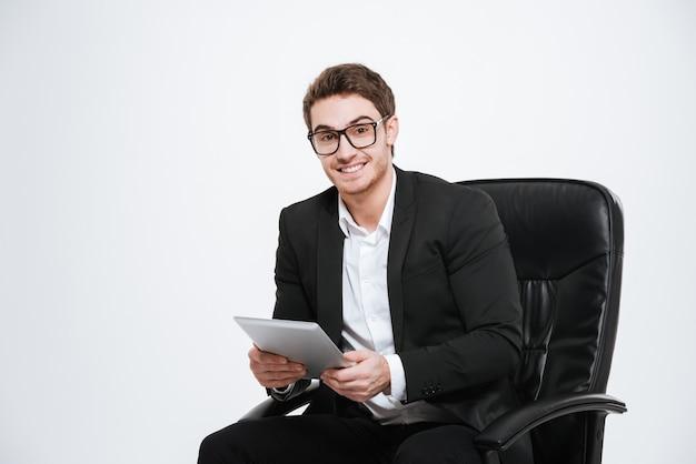Foto de jovem empresário alegre bonito sentado na cadeira usando o computador tablet. isolado sobre a parede branca.