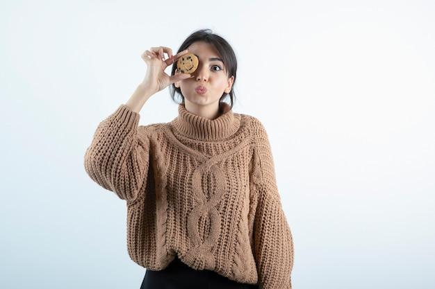 Foto de jovem escondendo os olhos atrás de biscoitos em fundo branco.