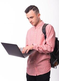 Foto de jovem, estudante, usando um laptop e em pé sobre o espaço isolado