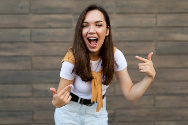 Foto de jovem feliz alegre morena atraente com emoções sinceras, vestindo roupa elegante em pé na rua perto de uma parede marrom e apontando para si mesma. conceito de estilo de vida.