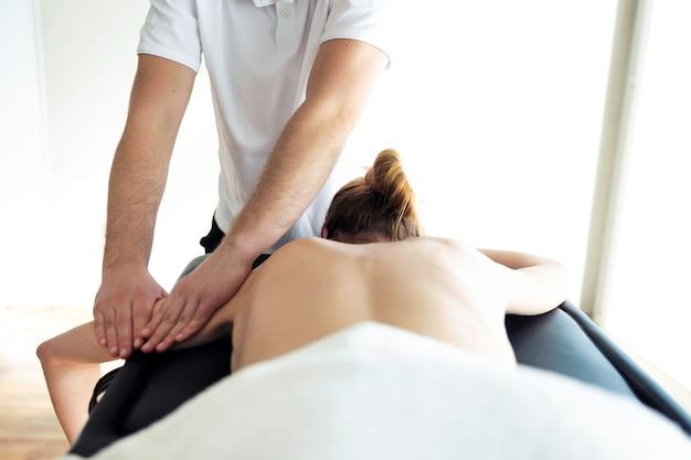 Foto de jovem fisioterapeuta fazendo tratamento de braços para o paciente em uma sala de fisioterapia. reabilitação, massagem médica e conceito de terapia manual.