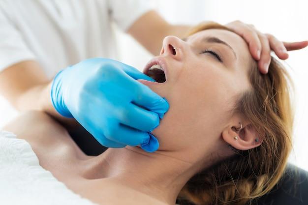 Foto de jovem fisioterapeuta fazendo um tratamento facial para o paciente em uma sala de fisioterapia. reabilitação, massagem médica e conceito de terapia manual.