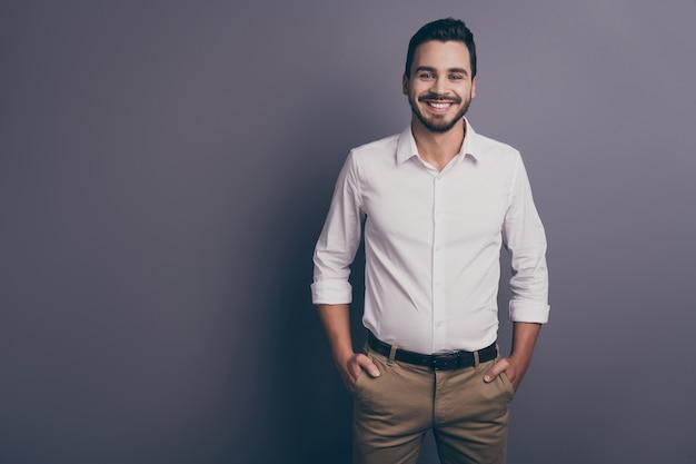 Foto de jovem homem de negócios machista com as mãos nos bolsos posando