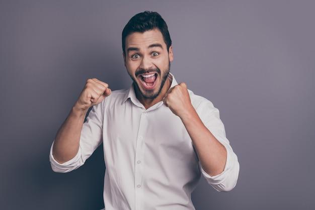 Foto de jovem homem de negócios machista segurando os punhos e boca aberta