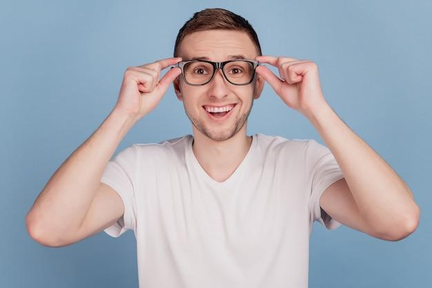 Foto de jovem infeliz espantado chocado surpreso notícias sorriso feliz mãos tocando óculos isolados sobre fundo de cor azul