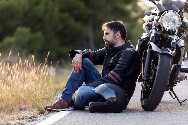 Foto de jovem macho sentado na estrada, encostado em sua motocicleta enquanto espera a assistência na estrada para consertar a moto.