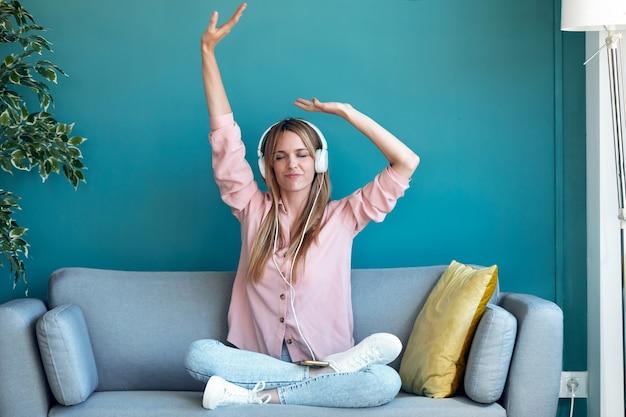 Foto de jovem motivada ouvindo música com o smartphone enquanto está sentado no sofá em casa.