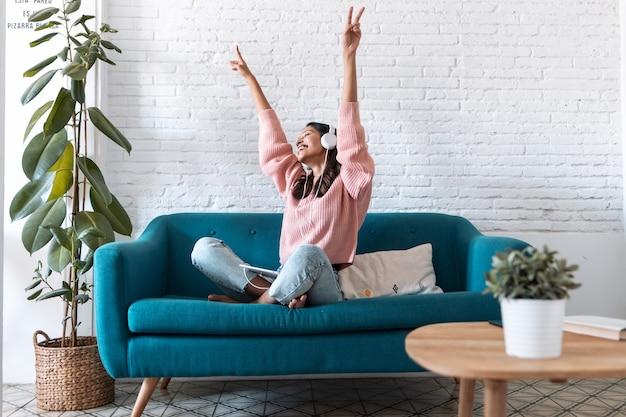 Foto de jovem motivada ouvindo música com tablet digital enquanto está sentado no sofá em casa.