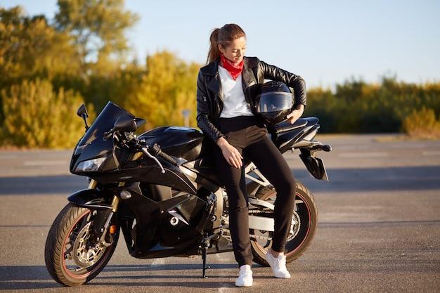 Foto de jovem motociclista feminina usa roupas da moda, tênis branco, segura o capacete debaixo do braço, fica perto de moto preta
