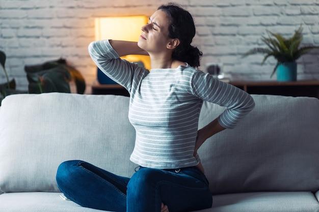 Foto de jovem mulher com dor nas costas e pescoço, sentada no sofá da sala de estar em casa.