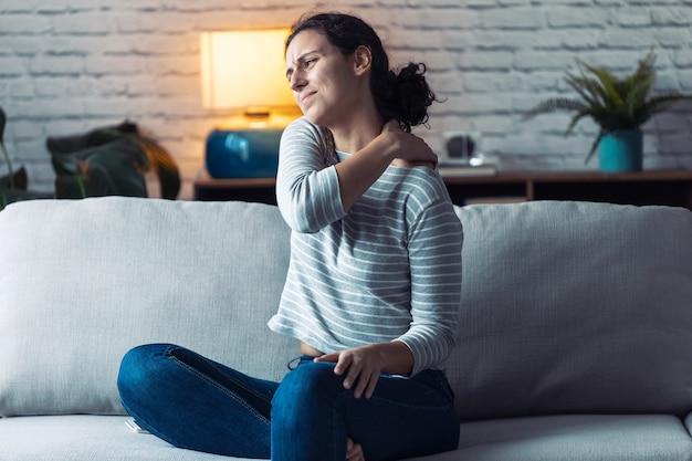 Foto de jovem mulher com dor nas costas, sentada no sofá da sala de estar em casa.