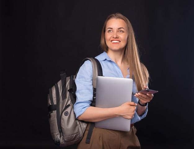 Foto de jovem mulher de negócios com mochila e usando smartphone sobre fundo escuro