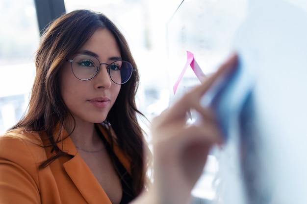 Foto de jovem mulher de negócios trabalhando no quadro branco com adesivos de post-it no escritório.