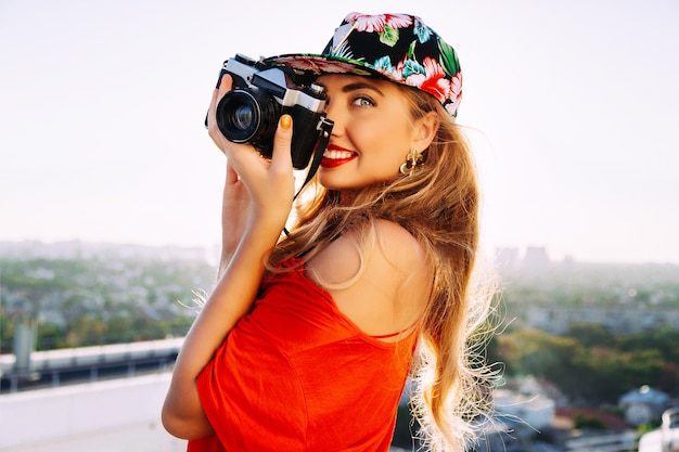 Foto de jovem mulher loira sensual sexy tirando foto na câmera retrô vintage hipster, sorrindo e se divertindo, usando chapéu brilhante floral muamba.