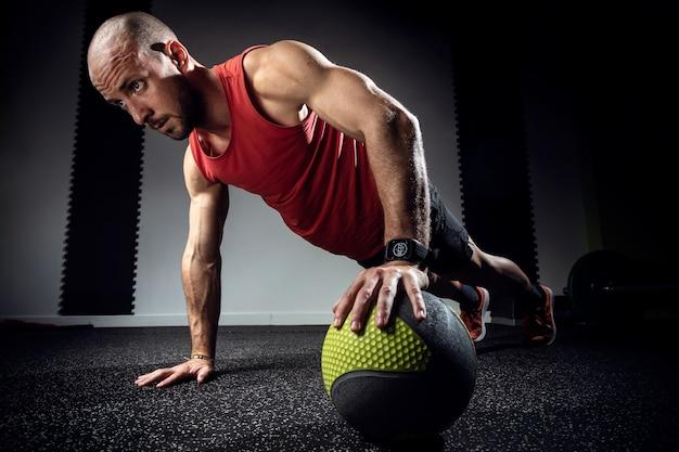 Foto de jovem musculoso fazendo flexões com bola de medicina no estúdio escuro.