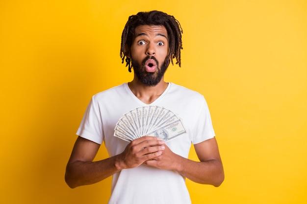 Foto de jovem negro chocado segurando salário, fã de dinheiro usa camiseta branca com fundo de cor amarela