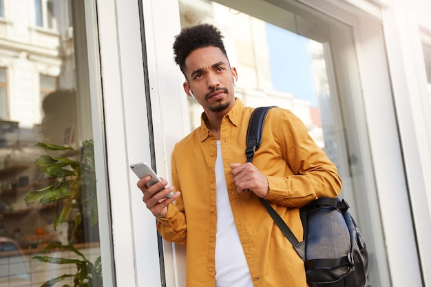 Foto de jovem pensando cara afro-americano de camisa amarela, andando pela rua, segura o telefone, ouvindo novo podcast, parece dúvida.