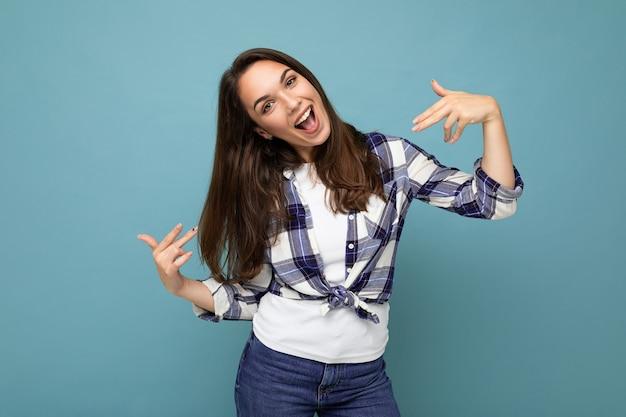 Foto de jovem positiva deliciosa sorridente linda mulher morena com emoções sinceras, vestindo a camisa da moda em pé isolado sobre um fundo azul com espaço livre e apontando para você mesmo.