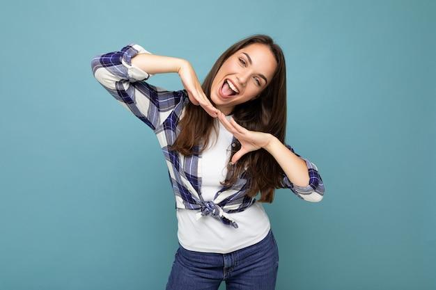 Foto de jovem positiva deliciosa sorridente linda mulher morena com emoções sinceras, vestindo camisa de seleção hippie em pé isolado sobre um fundo azul com espaço livre.