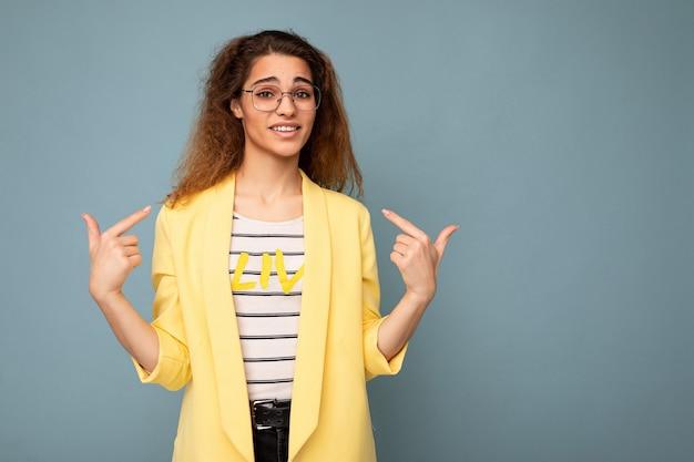 Foto de jovem positiva linda morena encaracolada com emoções sinceras vestindo amarelo casual