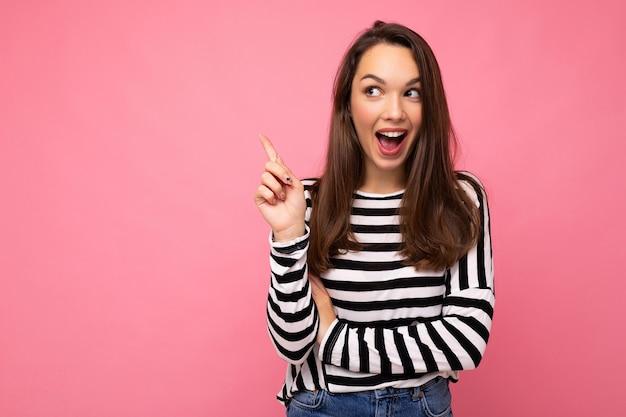 Foto de jovem positivo feliz surpreso bela mulher morena bonita com emoções sinceras, vestindo suéter listrado casual isolado no fundo rosa com espaço vazio e tendo uma ideia.