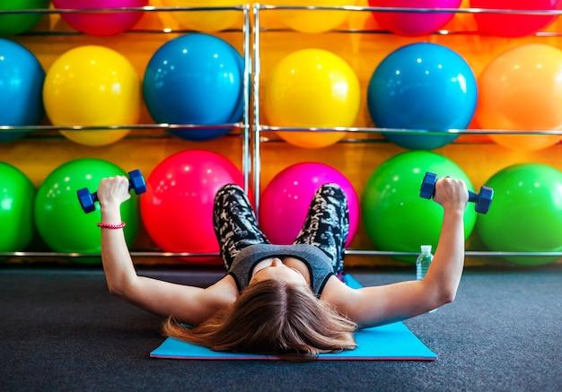 Foto de jovem se exercitando com halteres na academia