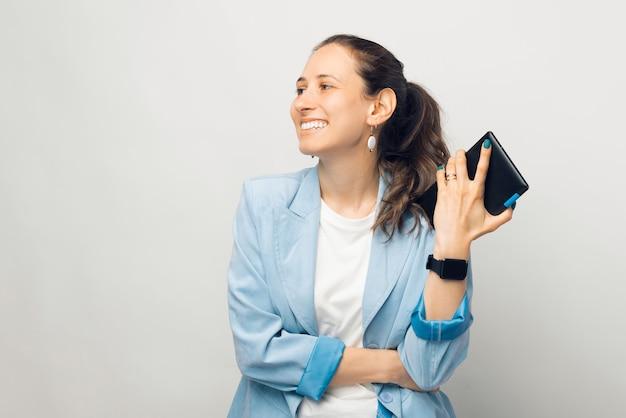 Foto de jovem sorridente alegre casual olhando para longe e segurando um tablet sobre fundo branco