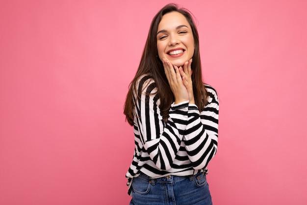 Foto de jovem sorridente feliz bonita morena positiva com emoções sinceras, vestindo pulôver listrado casual, isolado no fundo rosa com espaço de cópia.