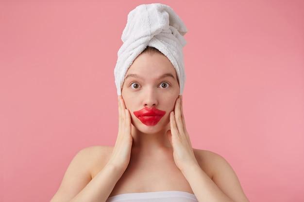 Foto de jovem surpresa após o banho com uma toalha na cabeça, olha, com os olhos bem abertos, com remendo nos lábios, ouve notícias, toca o rosto com as palmas das mãos, fica de pé.