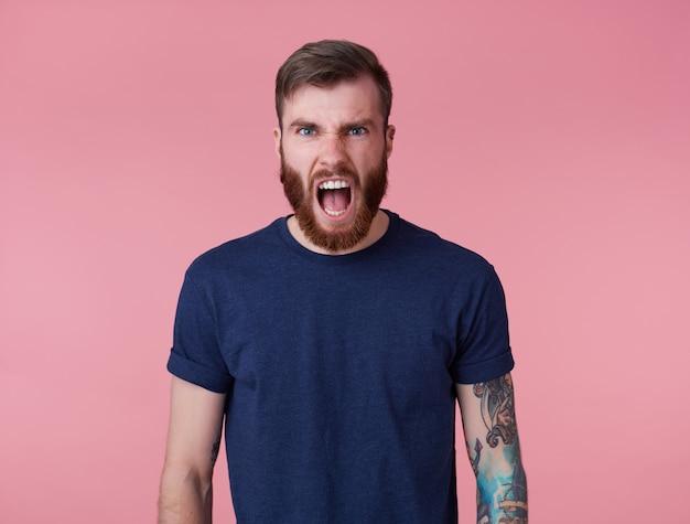 Foto de jovem tatuado homem barbudo vermelho em uma camiseta em branco, gritando e sentindo uma forte dor e raiva, fica sobre um fundo rosa.