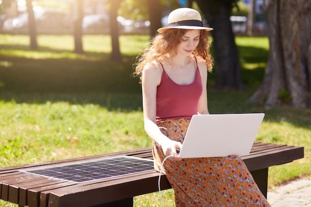 Foto de jovem trabalhando com laptop, carregando o dispositivo no banco inovador, construído na porta usb