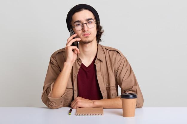 Foto de jovem usando telefone inteligente para conversa, discute idéias para nova starup, estudante do sexo masculino jovem hippie sentado à mesa do whte, bebendo café, vestindo casualmente. conceito de pessoas e negócios.