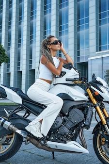 Foto de jovem vestindo roupas brancas da moda, sentado na moto do lado de fora.