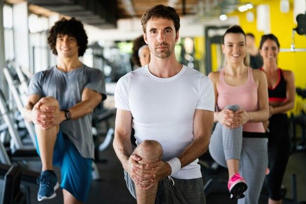 Foto de jovens amigos do time de fitness alegres na academia