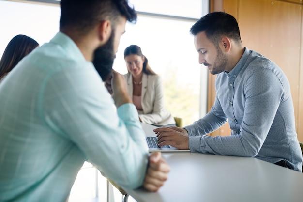 Foto de jovens arquitetos discutindo em um escritório moderno