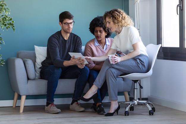 Foto de jovens empresários casuais trabalhando com o tablet digital enquanto estão sentados no novo escritório.